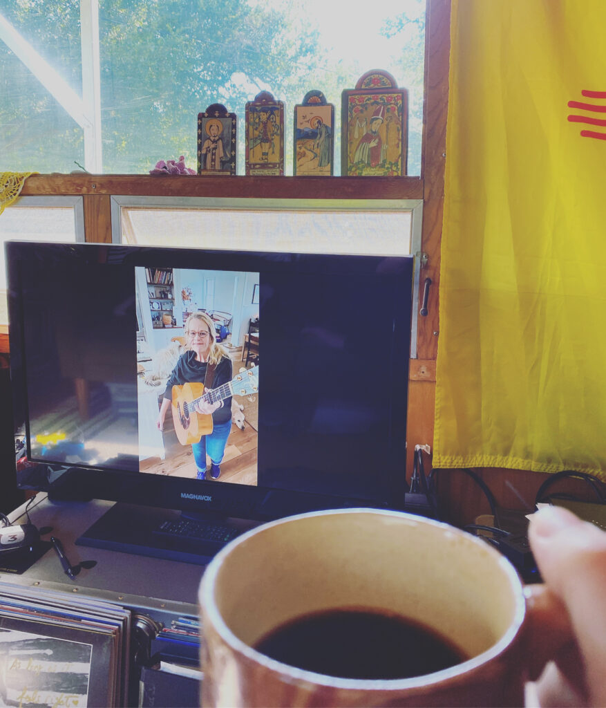 A coffee cup in front of Mary Chapin Carpenter playing guitar on a laptop screen, window behind.
